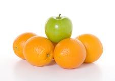 Über der Masse - grüner Apple zu den Orangen Stockbilder