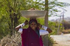 BERA, RAJASTHÁN, la INDIA, abril de 2014, mujer joven sonriente lleva el estiércol en su cabeza fotografía de archivo