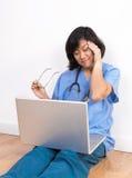 Überarbeiteter Frauendoktor oder -krankenschwester am Computer Stockfoto