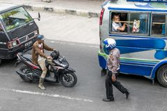 A policeman approaching the biker on busy street in Sumatra. Stock Images