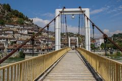 A pedestrian bridge over the river Lumi i Osumit overlooking the medieval white houses - Unesco heritage stock photos
