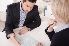Berater, der auf dem Tisch in einer Sitzung mit einem explainin des freien Raumes sitzt Lizenzfreie Stockfotografie