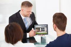 Berater, der Hausbild zu den Paaren auf Tablette zeigt Lizenzfreie Stockfotos