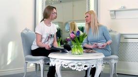Berater in einem luxuriösen Kleiderspeicher berät den Käufer, der nahe einem großen Spiegel sitzt stock footage