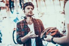 Berater Helps Guy Choose Helmet für Fahrrad-Fahrten lizenzfreies stockfoto