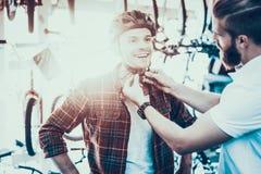 Berater Helps Guy Try auf Sturzhelm für Fahrrad-Fahrten lizenzfreies stockfoto