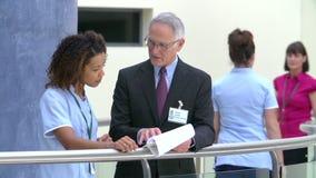 Berater Meeting With Nurse in der Krankenhaus-Aufnahme