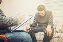 Beratungssitzung des Psychologen Deprimierter Mannbesuchspsychotherapeut, Doktor schreiben Anmerkungen Stockfotografie
