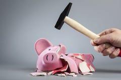 Berauben von Sparschwein mit Hammer lizenzfreie stockfotos
