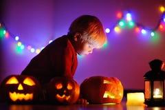 Berbeć chłopiec bawić się z Halloween baniami indoors Zdjęcia Stock