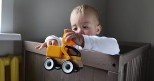 Berbeć chłopiec bawić się z kolorowym zabawkarskim ciągnikiem zbiory