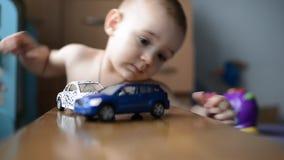 Berbeć chłopiec bawić się z zabawkarskim samochodem zdjęcie wideo