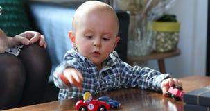 Berbeć chłopiec bawić się z zabawkarskimi samochodami zbiory