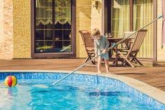Berbeć chłopiec czyści basenu i ciągnie piłkę z po Obrazy Stock