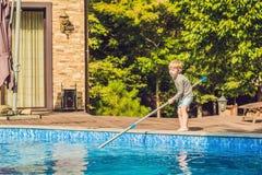 Berbeć chłopiec czyści basenu i ciągnie piłkę z po Zdjęcie Royalty Free