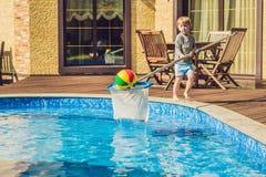 Berbeć chłopiec czyści basenu i ciągnie piłkę z po Fotografia Stock