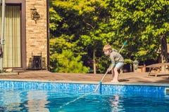 Berbeć chłopiec czyści basenu i ciągnie piłkę z po obraz royalty free