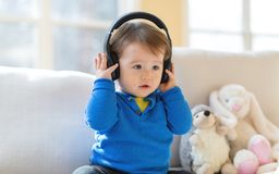 Berbeć chłopiec słucha muzyka z hełmofonami obraz stock