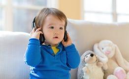 Berbeć chłopiec słucha muzyka z hełmofonami zdjęcie royalty free