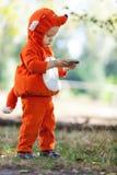 Berbeć chłopiec w lisa mienia kostiumowym smartphone Fotografia Royalty Free