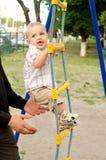 Berbeć chłopiec wstępująca linowa drabina outdoors Zdjęcie Stock