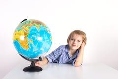 Berbeć chłopiec z kulą ziemską na lekcji praktyczny życie na białym tle, Montessori klasa, odizolowywa zdjęcie royalty free