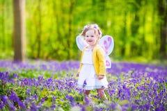 Berbeć dziewczyna w czarodziejskim kostiumu w bluebell lesie zdjęcie royalty free