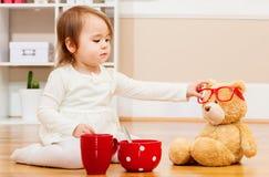 Berbeć dziewczyna ma herbacianego czas z jej misiem Obrazy Stock