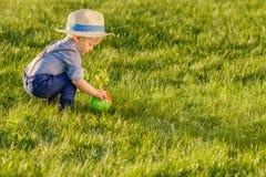 Berbecia dziecko outdoors Jeden roczniak chłopiec jest ubranym słomianego kapelusz używać podlewanie puszkę fotografia stock