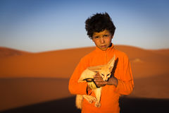 Berber child holding a desert fox poses in the Erg Chebbi dunes in Morocco. Stock Photography