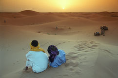 Berber guides. They live together, camel driver and the animals. Tourist guides rest on dunes and watching the sunset near Merzouga, Marocco Royalty Free Stock Photos