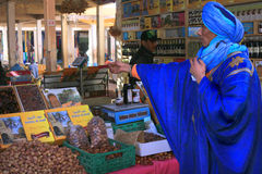Berber man buys dates. RISSANI, MOROCCO, FEBRUARY 22, 2016: Traditional Berber man dressed in traditional blue Tuareg clothing making a purchase in Rissani Souk stock image