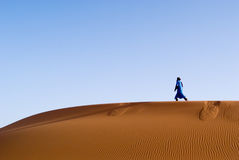 Berber man walking in a dune o. F erg chebbi at dawn Royalty Free Stock Photography