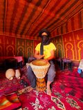 Berber Man on Zagora Desert in Morocco. Unidentified Berber man playing the drum inside of the tent on the Zagora Desert in Morocco, May 04, 2013. Berber people Royalty Free Stock Image