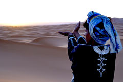Berber praying at dawn in the ERG desert in Morocco. Erg Morocco A Berber man prays facing the rising sun .Desert Erg Chebbi in Arabic: عرق الشبي is one Stock Photo