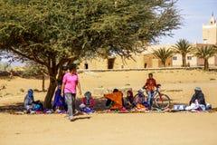 Berberförsäljare med turister i en moroccan by på en traditionell marknadsplats eller souq Royaltyfri Fotografi