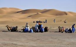 Berbers and camels at dunes,april 16,2012 royalty free stock photos