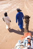 Berbers pulling a camel in the Sahara desert Stock Photo