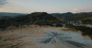 Flying forwards over mud volcanoes and lunar looking landscape. The Berca Mud Volcanoes Vulcanii Noroiosi de la Paclele Mici is a geological and botanical stock video footage