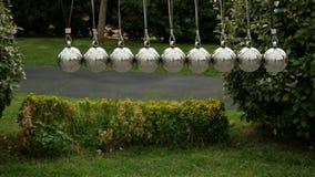 Berceau du ` s de Newton : un pendule avec les sphères de oscillation en métal en parc d'attractions en nature 4K banque de vidéos