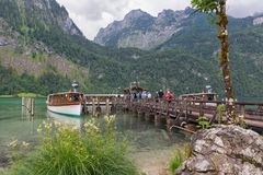 People on pier embarking launch ship at Konigssee. BERCHTESGADEN, GERMANY - JULY 08, 2017: People on pier embarking launch ship at Konigssee after a walk to the royalty free stock image