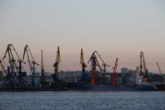 BERDIANSK - UCRANIA, EL 2 DE SEPTIEMBRE DE 2016: Silueta grande de muchas grúas en el puerto marítimo Imagen de archivo