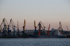 BERDIANSK - UKRAINE, LE 2 SEPTEMBRE 2016 : Silhouette de beaucoup grande de grues dans le port maritime Image stock