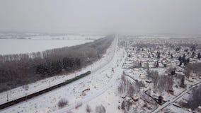 Berdsk, Rusland - Desember 30, 2018: Luchtfotografie Een goederentrein reist voorbij het dorp van Lebedevka stock videobeelden