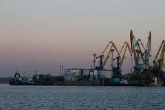 BERDYANSK - ΟΥΚΡΑΝΙΑ, ΣΤΙΣ 2 ΣΕΠΤΕΜΒΡΊΟΥ 2016: Σκιαγραφία πολλών μεγάλη γερανών στο θαλάσσιο λιμένα στοκ εικόνες