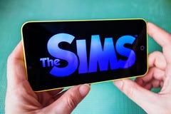 Berdyansk, Ucrânia - 4 de março de 2019 - feche acima da mão da pessoa que joga o apllication móvel do jogo de The Sims foto de stock