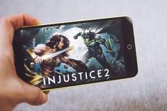 Berdyansk, Ucrânia - 4 de março de 2019: Mãos que guardam um smartphone com jogo da injustiça 2 na tela de exposição fotos de stock royalty free