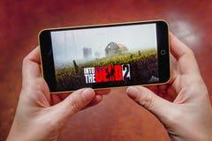 Berdyansk, Ucrânia - 17 de março de 2019: Mãos que guardam um smartphone com no jogo inoperante de 2 móbeis na tela de exposição, imagens de stock