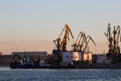 BERDYANSK - UCRANIA, EL 2 DE SEPTIEMBRE DE 2016: La silueta grande de muchas grúas en el puerto en la luz de oro de la salida del Foto de archivo