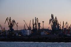 BERDYANSK - UCRANIA, EL 2 DE SEPTIEMBRE DE 2016: Silueta grande de muchas grúas en el puerto marítimo Imágenes de archivo libres de regalías
